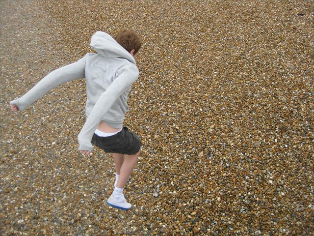 Me jumping onto the pebbles on a beach at Lyme Regis