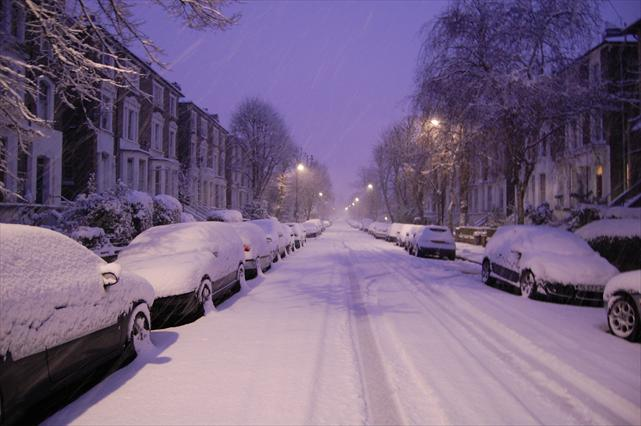A snow covered London street on a snowy day.